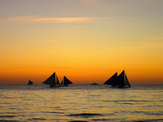 Sailboats cruise by Boracay Island, decorating the horizon after a bright sunset