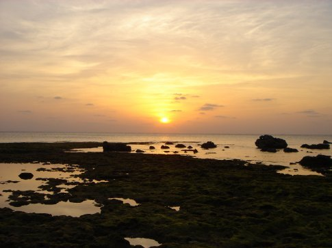 Sun setting over coral reef.