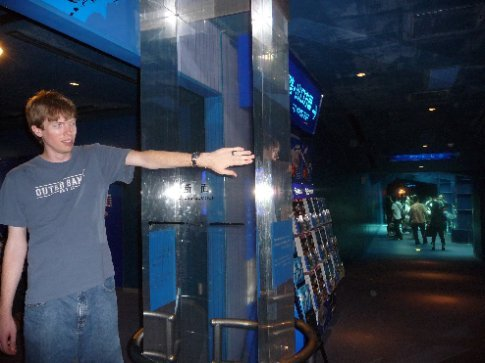 Brandon shows just how thick the glass is on the Aquarium's whale shark and manta ray tank.