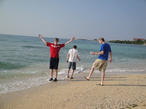 The three boys clowning around in the sea.
