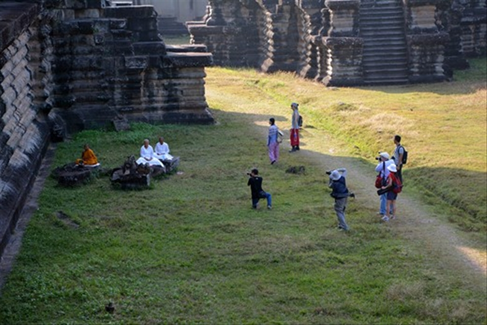 Buddhist monks meditating at Angkor Wat caught attention of tourist photographers