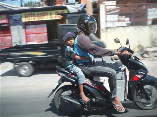 Motorbike with child snoozing.