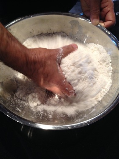 Mixing puttu: rice flour, salt, coconut flakes and water with hand