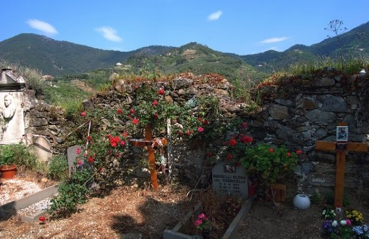 Flowers and trinkets bedeck the newest graves in an ancient cemetery in Cinque Terre.