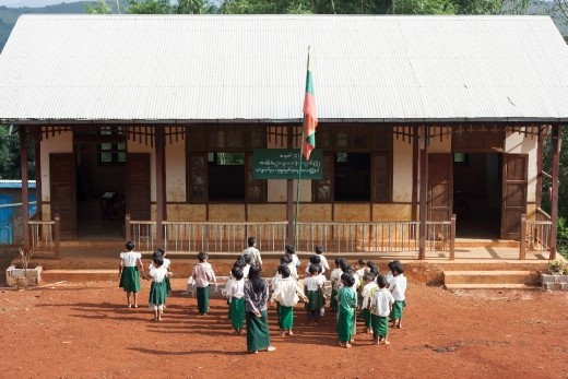 Local Burmese kids singing in front of the flag and school before the class begins