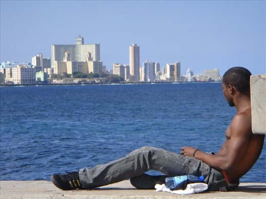 A young Cuban relaxing in Malecon dreaming of a life that  he probably doesn't even want while the time slowly passes by....