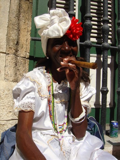 A Cuban woman in traditional Cuban attire posing for tourists with a constant smile on her face. Is this the reality?