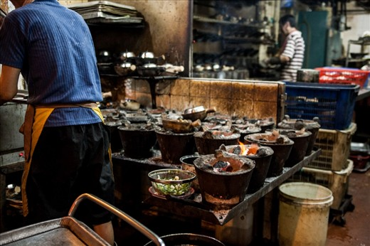 One of the preferred way of cooking things is using a wok pan. Wok is perfect for frying things quickly as the temperature is concentrated in the bottom of the pan. In this photo you can see the the wok stoves where food is cooked.