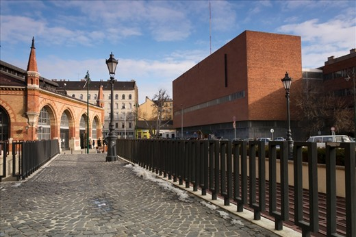 The beautiful old marketplace, Budapest, across a strange brick structure and large metal fence.