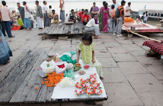 """The whole city is a gigantic bazaar – everyone is peddling something. This little girl was making """"donas"""" – bunches of marigold and roses with an earthen lamp, all arranged in a leafy bowl. I wonder what these are for..."""