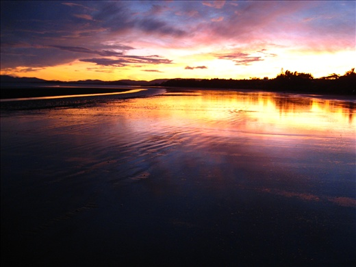 Nightfall slowly creeps into the horizon as if to somewhat swallow the breaking dusk. This landscape shot captures the reflective image of the sunset which is magnificently mirrored over the low tide shore line.