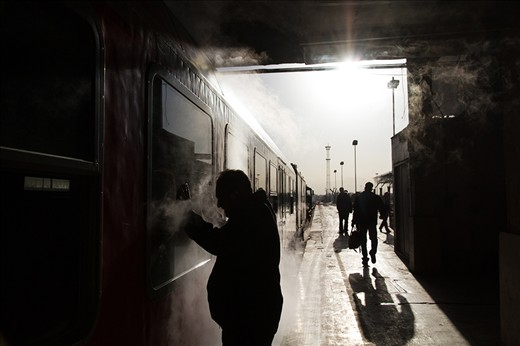 A man is bidding farewell to his family behind a train window as the train is waiting in Tehran's main train station and is about to set off to Mashhad on a mild winter morning. Oddly for any public place in Iran, photography is often times allowed in and outside trains; a culture about the roots of which I'm unaware.