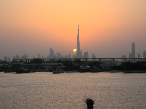 Sunset across The Dubai Creek looking at Downtown Dur Dubai and the Burj Dubai, the worlds tallest structure.