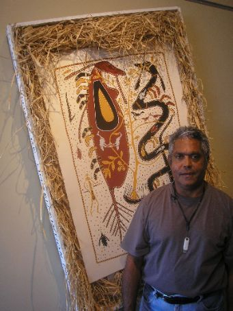 Glen standing on a brilliant painting depicting the yin yang of indigenous art