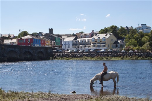 The early morning horse fair ended, a Gypsy boy rides his horse bareback into the River Laune to escape the heat and dust while the colorful town of Killorglin sits in the background.