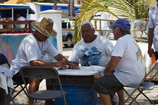 While some of the fishermans prepare the nets for the next day, others play dominoes to pass the time.