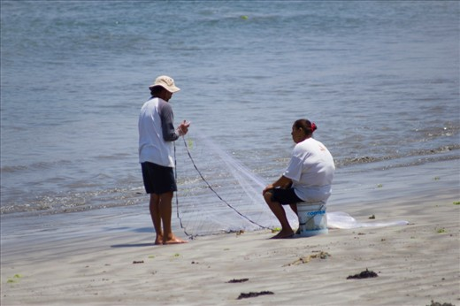 A man tries on shore fishing while his wife waits.