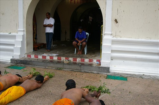 Onlookingers watch rollers past temple doors during Thimithi festival , Juvenile males don't roll around the temple but participate by watching the spectacle of endurance .The neem leaves are to ward off evil