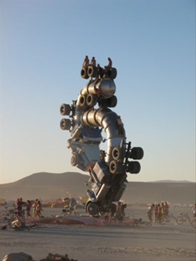 This photograph showing a fusion of two trucks joined to create one piece of artwork that could be climbed into and viewed from various angles. These characters are sitting on top of the highest point to watch sunset stark naked over the black rock mountains in the Nevada desert. I tried climbing inside the truck but didn't seem to have the strength , which made me appreciate the position they were in. The concept of this piece shows a positive outlook of two trucks colliding.