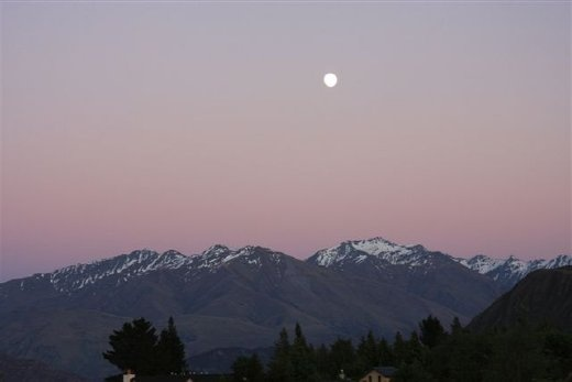 Sun coming up, with moon over the mountains, as seen from our room at Wanaka