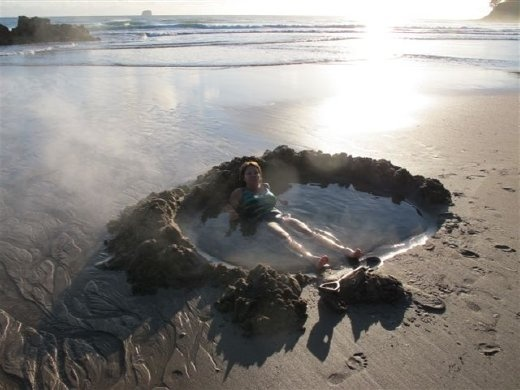 Lounging in a home-made hot tub in the sand at Hot Water Beach