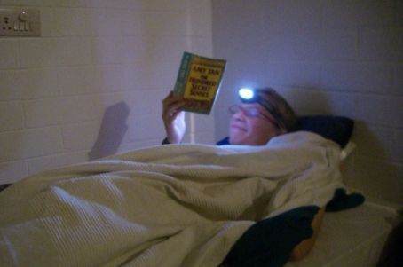 Kirsten reading with her head lamp
