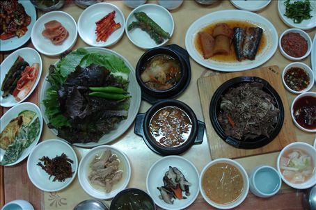 Traditional dinner - soup, lettuce for wrapping your food up into little parcels, beef, squash, mini anchovies, squid, various stems and veg, miscellaneous grey squares, tuna, and of course, makolli, Korean wine.