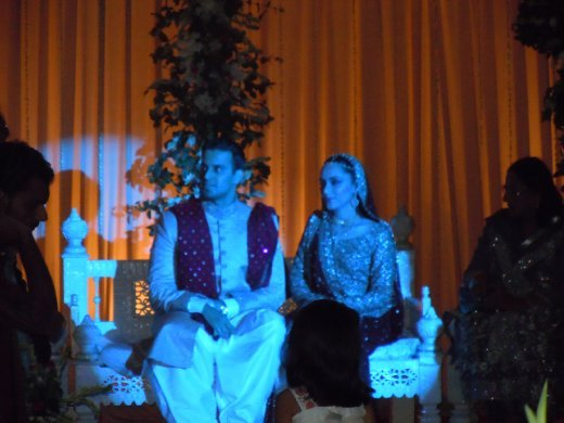 Bride and groom, in blue light at the reception.