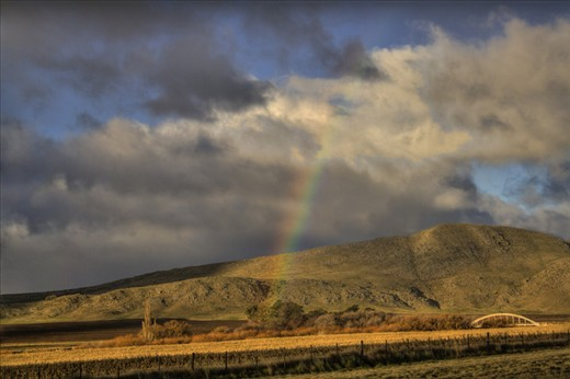 Rainbow, sun and big stormy clouds on the gold field and hills