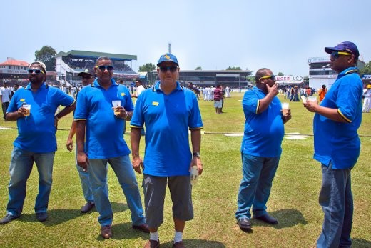 Some Royal College old boys in 'fine fashion' at the tea break, walking around the ground during the tea break.