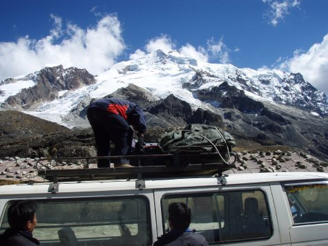 Our guides unloading the gear with the mountain in the background. If you look really closely you´ll see the high camp refugio above the guides back just on the snow line.