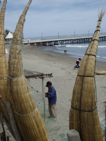 Fisherman fixing up his nets with the traditional fishing craft in foreground.