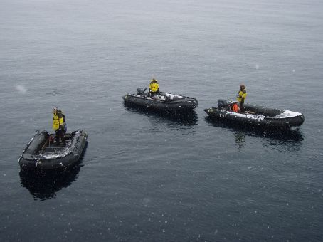 Zodiacs waiting for us. Note the calm water and the snow!!