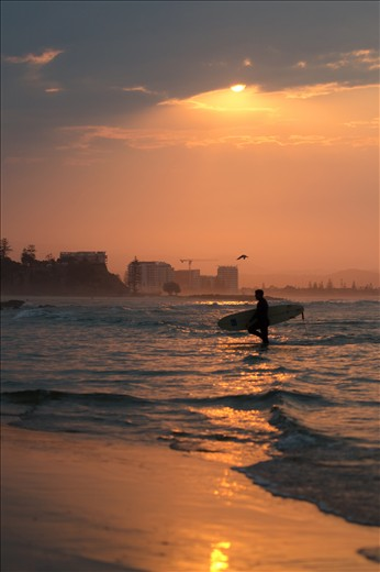 A Lone surfer is rewarded with a glimpse of brilliant sunset.