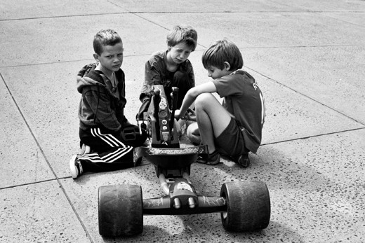 3 local kids trying to fix their broken trike which i repaired for them.