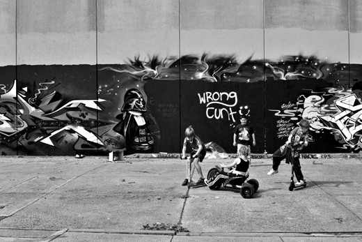 innocent street art and street kids playing on their newly repaired tricycle