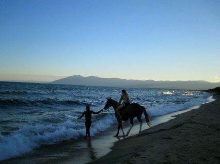 Beckie taking the horse for a swim, Kande beach, Malawi