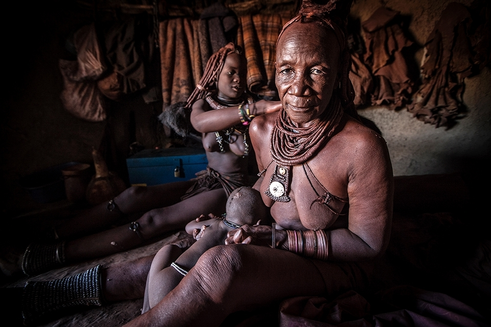 The Ochre is mixed with portions of thickened butter fat which is smeared all over the women's body to produce a bright red sheen. All of the females pitch in to help each other access areas that a single woman cannot. All of the Himba women share the work load in a village regardless of the task, their age or stature.
