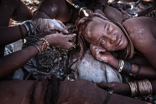 Once the daily chores are completed and the days temperature begins to soar, the women retreat back to the shade where their beauty salon continues. A Himba woman's hair is drawn into dreadlocks and encased in a thick ochre casing which adds to their beauty, but it is a laborious process that requires all hands to assist removing and replacing the delicate casing every 4 weeks or so.
