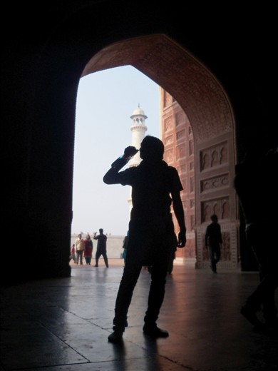 silhouette of man drinking water, standing between the gate.