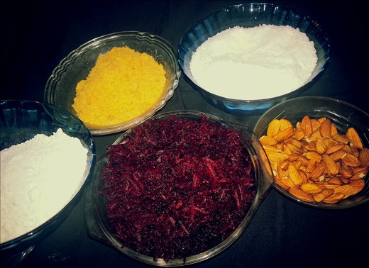 the ingredients of the dish - center maroon color is - grated beetroot, on the right to beetroot is almond, behind almonds there is a bowl of coconut shavings,beside it lies jaggery powder and on to the left of jaggery lies blended/powdered oats