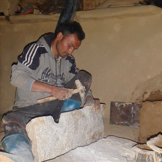 Working with sedimentary rock Dinesh is fashioning holes for the stove top.