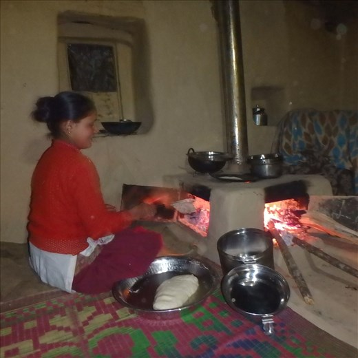 Hansi in roti production. When cooking is finished the roti door is closed and at the end of the night the front door is closed. Radiating thermal mass keeps the room warm through the night. And for the first time windows and doors can be closed!