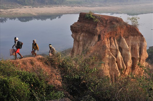 Tribal people ascend from river bed and overcome the barrier of