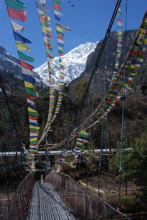 Prayer flags over bridge leaving the town of Chame