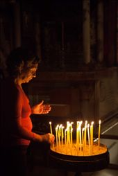 An older woman lighting candles in the near darkness of The Church of the Holy Sepulchre a few steps from the Golgotha altar, despite a crush of people from around the world, the woman had the space to herself and a moment of silence.: by brian_arnold4, Views[111]