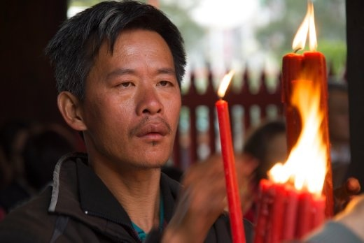 A temple worker stays in near constant motion arranging the myriad of candles at the Longshan Temple in Taipei, Taiwan. Although Buddhism has been a part of Taiwanese culture for more than three centuries, the last 25 years have seen a dramatic increase in the number of practicing followers.