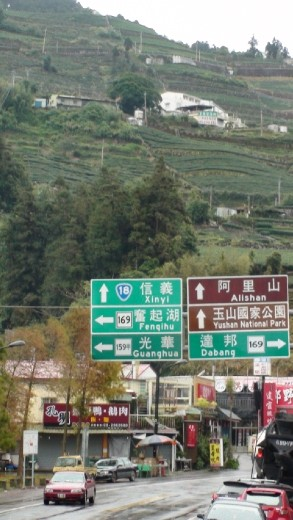 Tea terraces behind the sign showing the way to Ali Shan