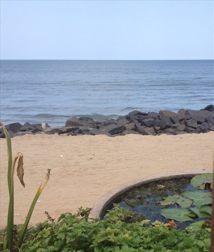 Beach view between the iron bars of Le Cafe
