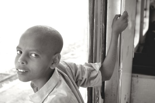 A curious boy watches as his country passes by